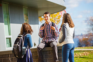 Students talking in front of a hall