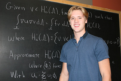 Student working on equation on blackboard