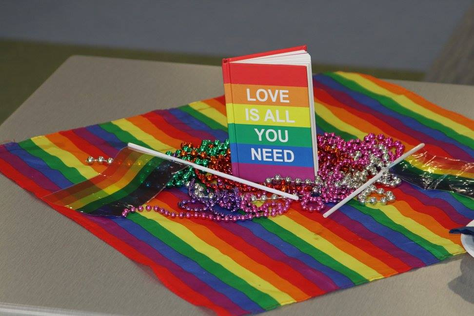 "Queer pride themed decorations with a book cover reading ""Love is all you need."""