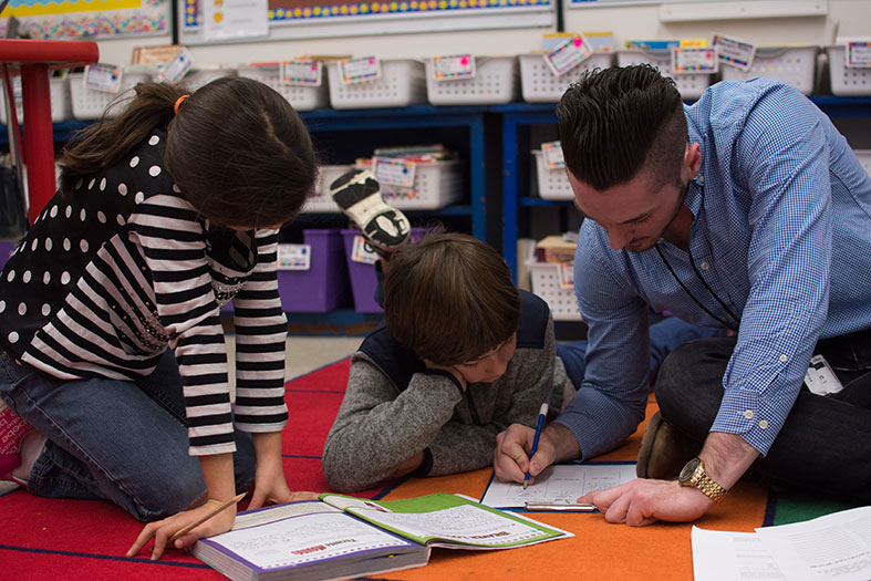 A picture of a teacher working with two students