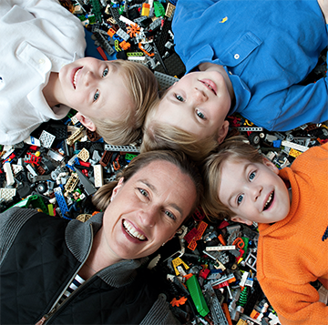 Amy Fazackerley and her three sons lay on a pile of legos