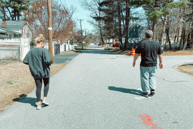 Two people walking in the road.