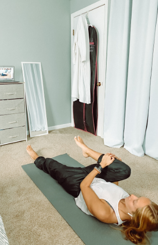 Person doing a yoga stretch on the floor.