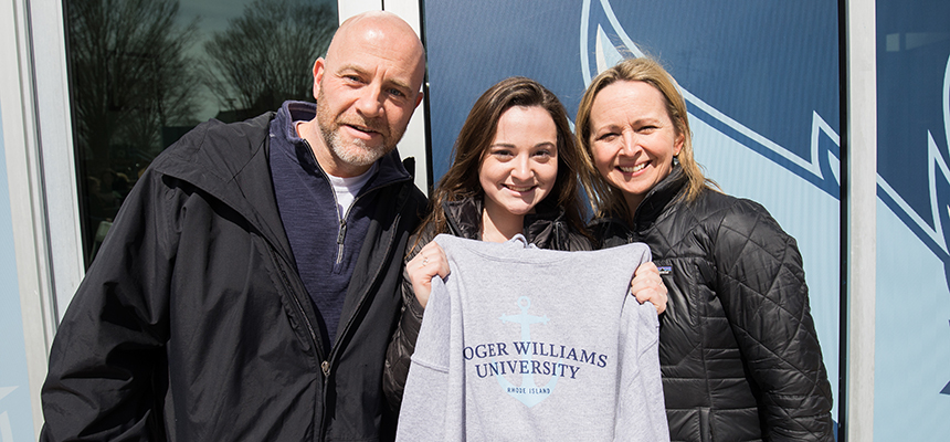 image of admitted student with parents after getting RWU sweatshirt at ASD 2019