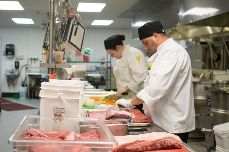 Chefs cutting meat