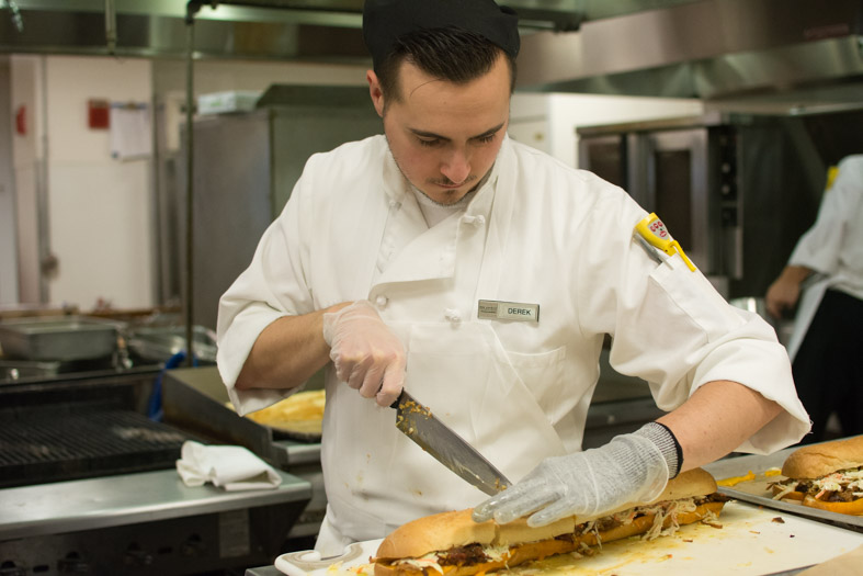 RWU chef cutting pork sandwich