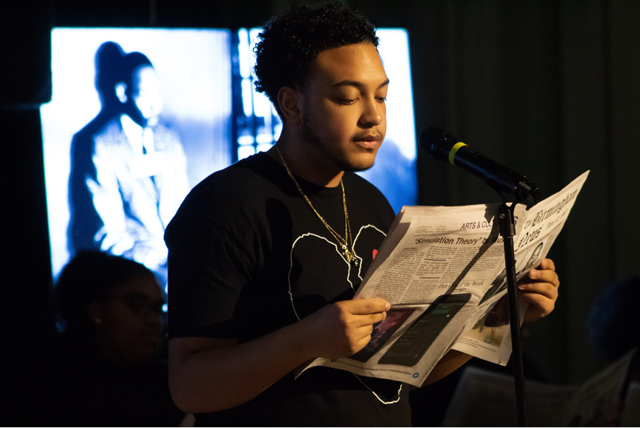 A student standing in front of a microphone during a Black History Month performance.