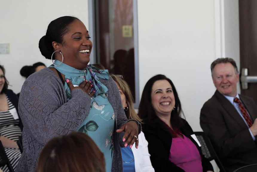 image of Morganna Beltre, school certifying official at University COllege in Providence, reacts to her award as University College Woman of the Year. Hawks Herald / Kayla Ebner