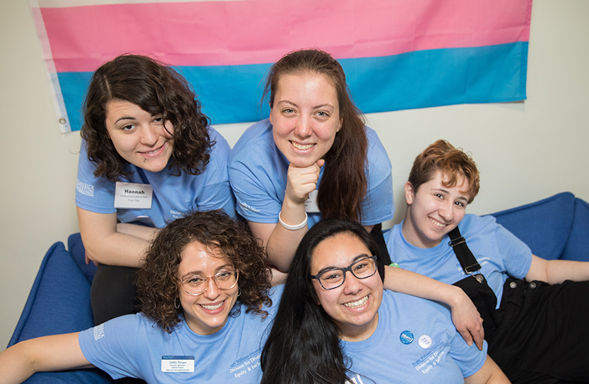 image of current RWU students and staff in the Queer and Trans Resource and Advocacy Center in front of the trans pride flag.