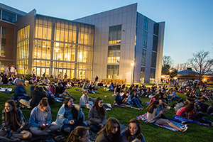 Students sitting outside on campus at night