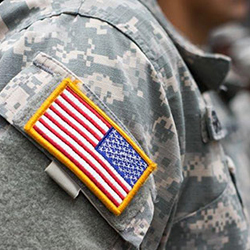 A close up of the american flag patch on the shoulder of a person in army fatigues.