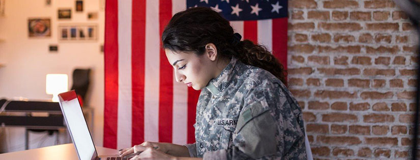 A woman in military fatigues works on a laptop.