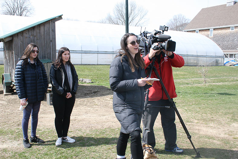 Journalism students observe an alumna reporting the news.