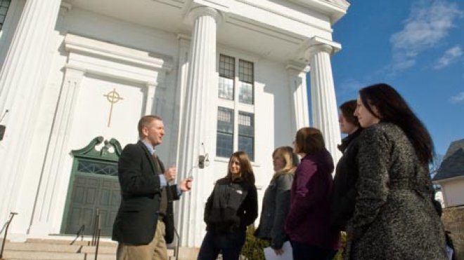 Professor lectures students on the steps of a historic building.