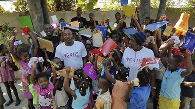 An alumnus poses with a group of schoolchildren in Haiti, where he brought supplies and disaster aid.
