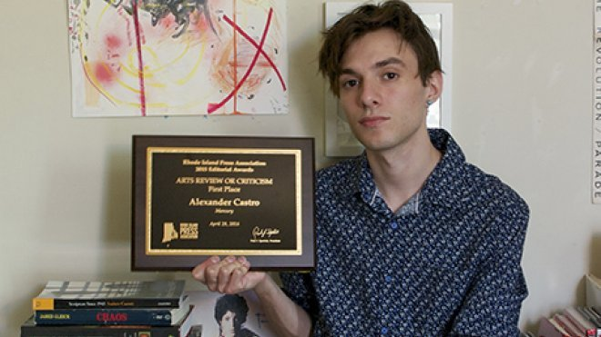 An alumnus holds his journalism award.
