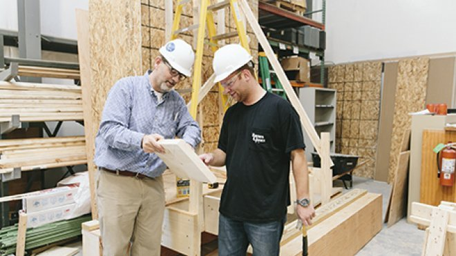 A student and professor work inside a construction lab.