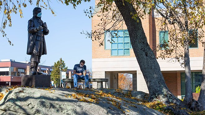 image of student sitting near Roger statue, both wearing masks