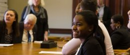 A student is smiling as she listens to a discussion between students, faculty and local elected officials