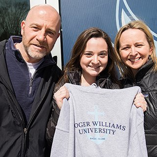 image of an RWU accepted student getting her sweatshirt, with her parents