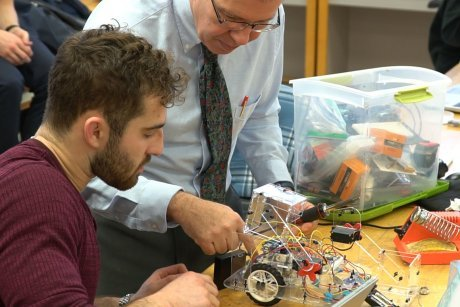 Engineering student repairs robot with help from Professor