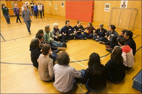Training participants sit in a circle with linked arms.