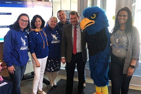 President Miaoulis poses with RWU's mascot and employees.