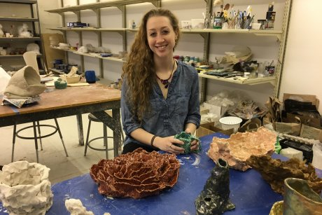 Student seated in the ceramics studio, surrounded by her art.