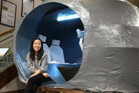 Student Hien Ngo sits inside her model Mars rover.