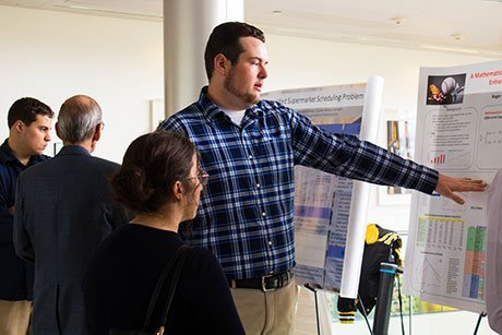 Student discusses his research at the Student Academic Showcase and Honors.