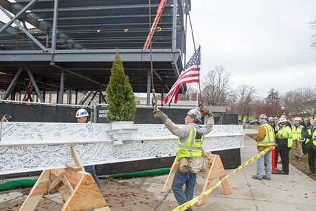 Construction crews prep the steel beam to be hoisted.