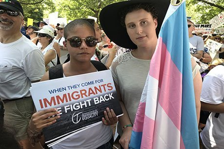 Two people standing with a flag and a sign.