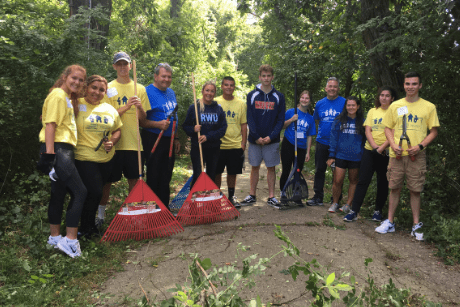 Group photo of students and president holding rakes on a path.