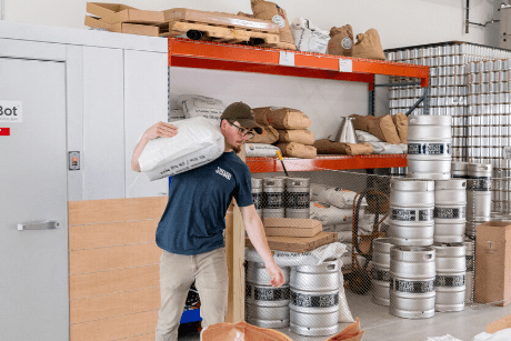 MacConnell carrying bag of malt across brewery.