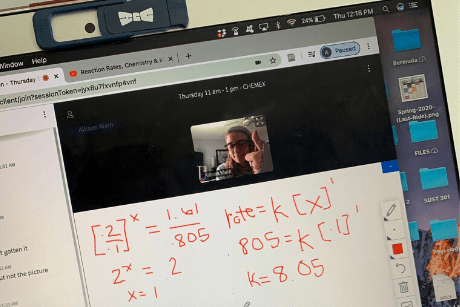 Photo of laptop showing equations written on a virtual whiteboard and student giving a thumbs up.