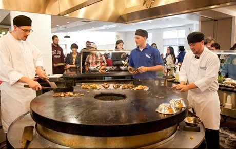 Chefs prepare food in dining hall