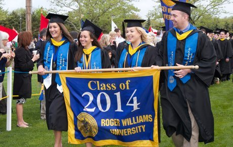 Graduates process with class banner