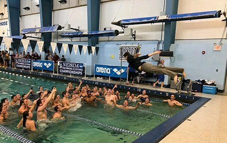 A student dives into a pool while his teammates celebrate their victory.