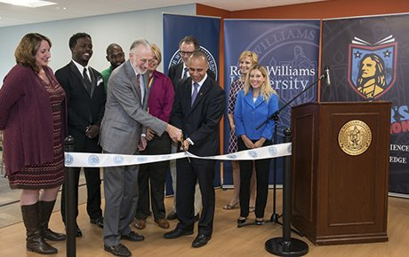 University administrators gather with state and city officials to cut the ribbon on a new campus building.