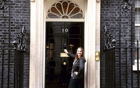 A student stands in front of the headquarters of the British government.