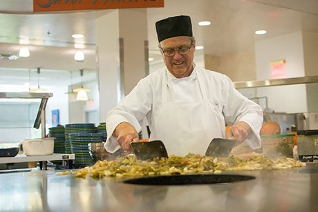Chef prepares food in Upper Commons.