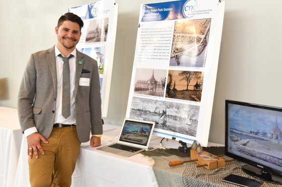Historic Preservation student stands with his community project at the Community Engagement Celebration
