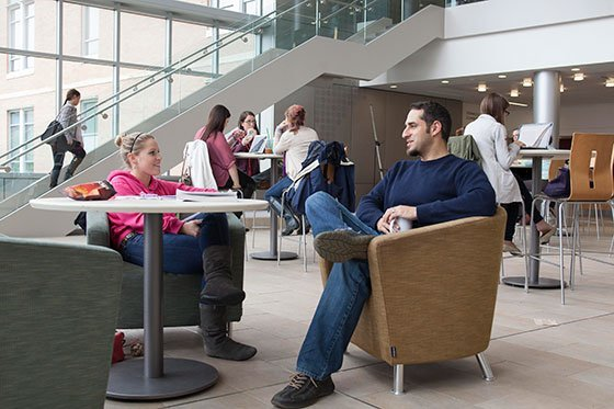 Professor talking with student in lounge.