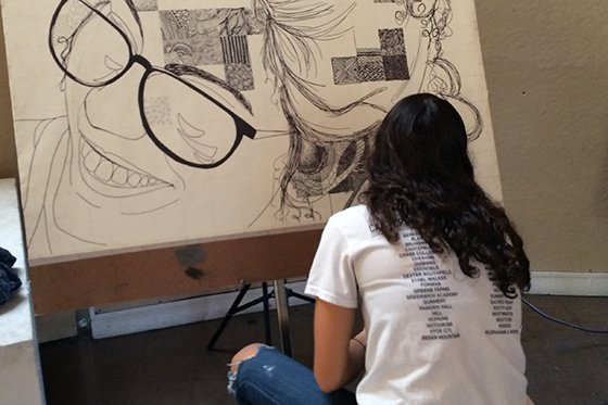 A female student working on a self portrait drawing.