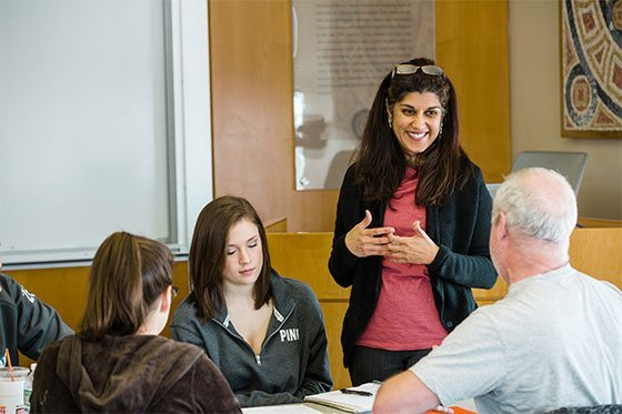 Communications professor working with students.