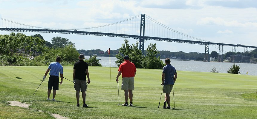 image of RWU alums golfing during Alumni Reunion Weekend with Mt Hope Bridge in background