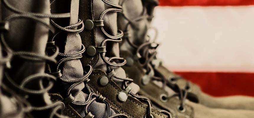 A close up photo of army boots with an American flag in the background.