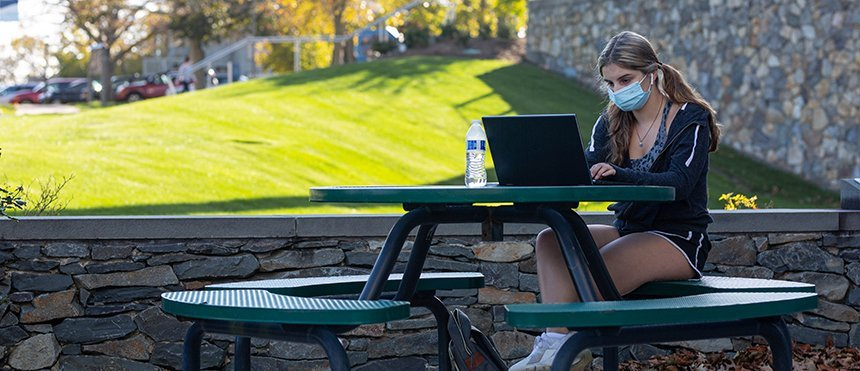 a student studies outside during RWU Summer Sessions on the Bristol campus