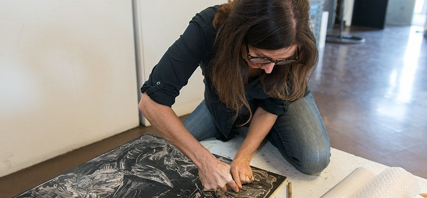 A VARTS professor working on a woodcut print